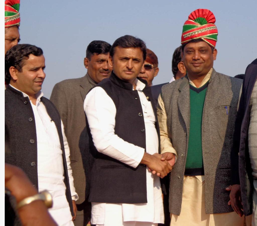 पगड़ी पहनाने के बाद पहलवान से हाथ मिलाते मुख्यमंत्री अखिलेश यादव व साथ में खड़े हैं सांसद धर्मेन्द्र यादव