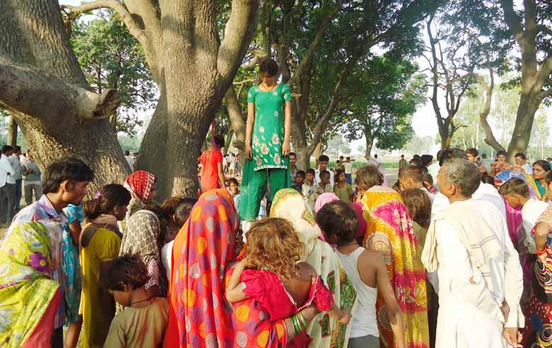 आम के पेड़ पर लटके दोनों बहनों के शव और मौके पर लगी भीड़।