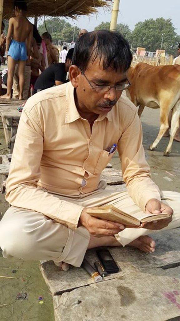 अयोध्या में सरयू तट पर पुस्तक में पढ़ कर जप करते विवादित एसओ गंगा सिंह यादव।