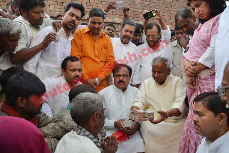 कटरा सआदतगंज में मृतक लड़कियों के परिजनों को रूपये देते हुए फोटो कराते वरिष्ठ भाजपा नेता।