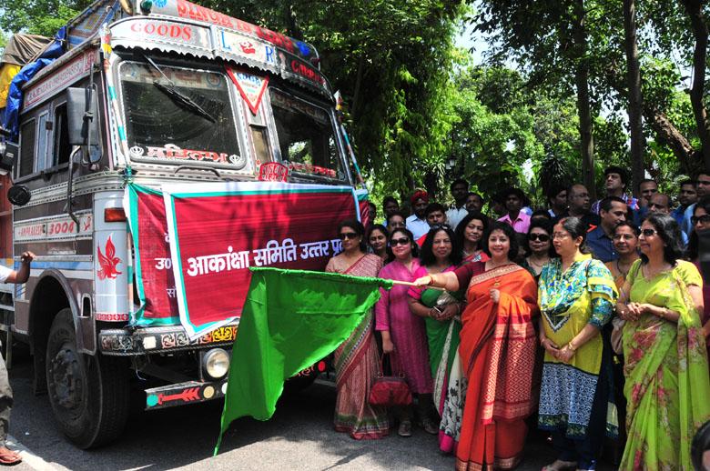 राहत सामग्री से भरे ट्रकों को हरी झंडी दिखाकर रवाना करते हुए आकांक्षा समिति की प्रदेश अध्यक्षा सुरभि रंजन।