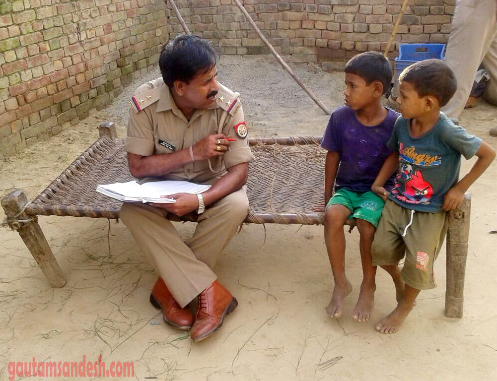 बच्चों से घटना के संबंध में जानकारी लेता पुलिस अफसर।
