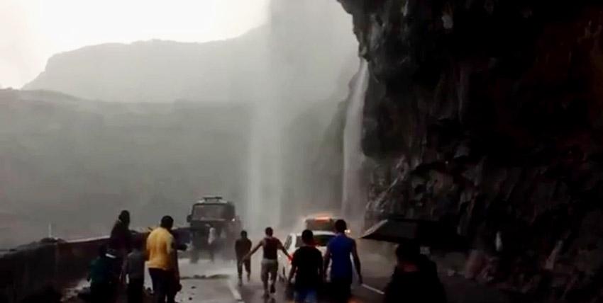 अचानक बने झरने के नीचे से गुजरते वाहन और आनंद लेते पर्यटक।