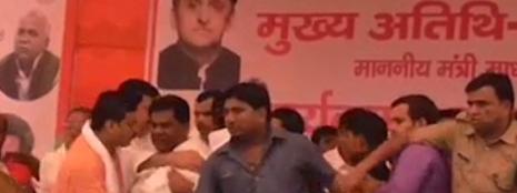 घटना के समय दर्जा राज्यमंत्री प्रदीप यादव को बाहों में जकड़े कार्यकर्ता।